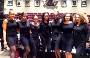 Seven panelists wearing black dresses standing with their arms around each other.