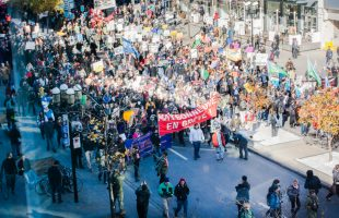"""A photo showing a street full of people holding a red banner saying """"Maisonneuve en greve."""""""