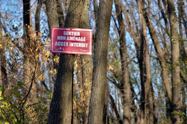 "Red sign saying ""uncleared trail. Access prohibited."" (translated from French) on a tree in Marie-Victorin Park."